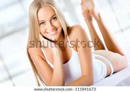 Beautiful blonde woman lying on the bed and smiling