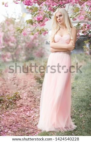 Beautiful blonde woman model standing in the spring gardens, blooming pink sakura, flying pink dress. Fine art portrait.