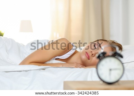 Beautiful blonde woman peacefully lying in bed sleeping early morning while alarm clock going to ring awakening. Early wake up, not getting enough sleep, oversleep, getting work time concept