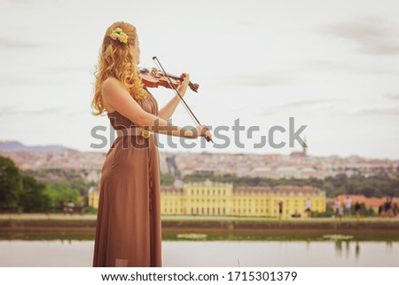 Beautiful blonde woman plays the violin outdoors. Violinist outdoors.