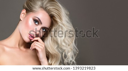 Beautiful Blonde Woman Portrait with blue eyes and Healthy Long Shiny Wavy hairstyle. Volume shampoo. Blond Curly permed Hair and bright makeup.  Beauty salon and haircare concept. #1393219823
