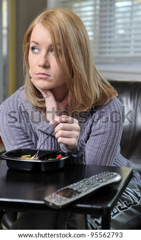 Beautiful blonde woman sitting in chair in pastel sweater eating a frozen (TV) dinner - sad looking off in distance