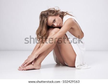 Beautiful blonde woman sitting on white background