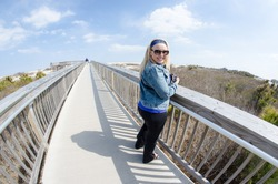 Beautiful blonde woman stands on the elevated boardwalk in Assateague Island National Seashore