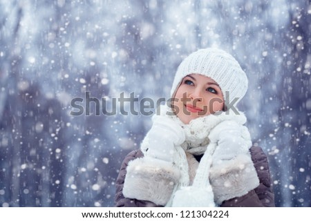 beautiful blonde woman walking outdoors under snowfall