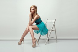 Beautiful blonde woman wearing a blue dress and high heels, sitting on a chair. Studio shot.