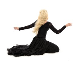beautiful blonde woman wearing a long black gothic gown, sitting on the ground.  isolated on white background.
