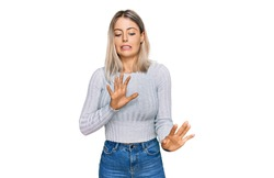 Beautiful blonde woman wearing casual clothes disgusted expression, displeased and fearful doing disgust face because aversion reaction.
