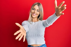 Beautiful blonde woman wearing casual clothes looking at the camera smiling with open arms for hug. cheerful expression embracing happiness.