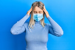 Beautiful blonde woman wearing covid-19 medical mask suffering from headache desperate and stressed because pain and migraine. hands on head.