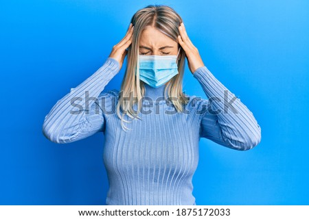 Beautiful blonde woman wearing covid-19 medical mask suffering from headache desperate and stressed because pain and migraine. hands on head.  Foto stock ©