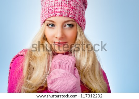 beautiful blonde woman wearing pink knitwear over blue background looking to the side