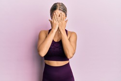 Beautiful blonde woman wearing sportswear over pink background with sad expression covering face with hands while crying. depression concept.