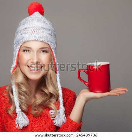 Beautiful blonde woman with an aromatic hot coffee in hand.