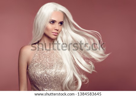 Beautiful Blonde Woman with blowing wavy hair. Portrait Of Young Sexy Blond Model With Beauty Makeup, long white hair style. Gorgeous lady posing isolated on brown studio background. #1384583645