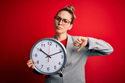 Beautiful blonde woman with blue eyes wearing glasses doing countdown using big clock with angry face, negative sign showing dislike with thumbs down, rejection concept