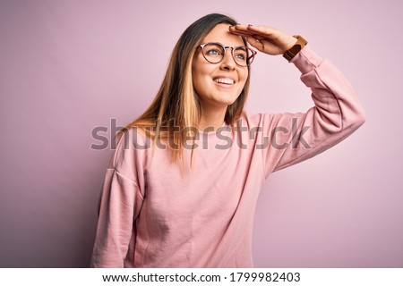 Photo of  Beautiful blonde woman with blue eyes wearing sweater and glasses over pink background very happy and smiling looking far away with hand over head. Searching concept.