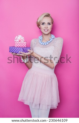 Beautiful blonde woman with cream colored dress holding pink and purple gift boxes. Studio portrait over bright pink background