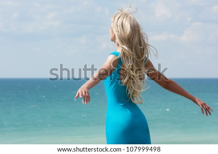 beautiful blonde woman with open hands at the blue sea and sky