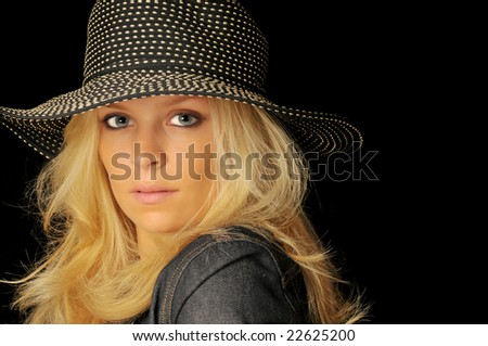 Beautiful blonde woman with spotted hat and denim jacket on black background.