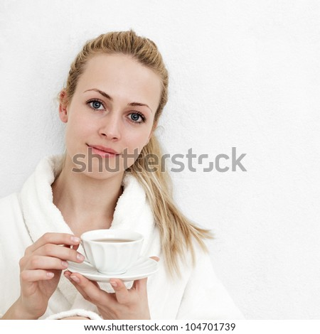 Beautiful blonde woman with tea against room wall