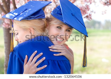 Beautiful Blonde women in blue gowns embracing celebrating their graduation