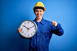 Beautiful blonde worker woman with blue eyes wearing security helmet holding big clock annoyed and frustrated shouting with anger, crazy and yelling with raised hand, anger concept