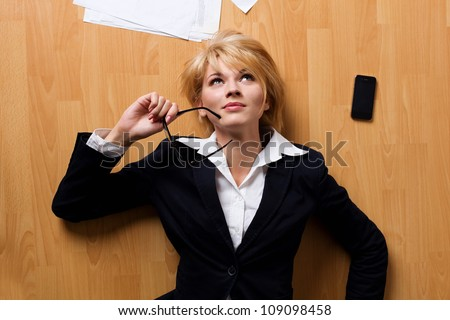 Beautiful blonde young businesswoman lying on floor - stock photo