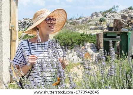 Beautiful blonde young female traveler wearing straw sun hat enjoying summer on Mediterranean cost strolling among lavander flowers on traditional costal village garden.