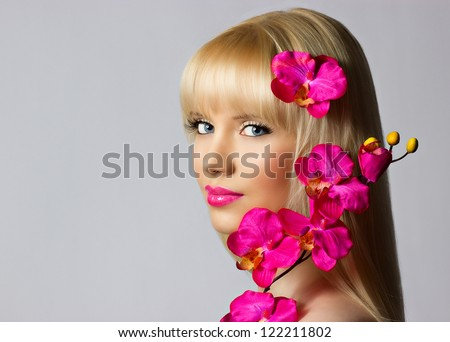 Beautiful blonde young girl with orchid flowers on grey background