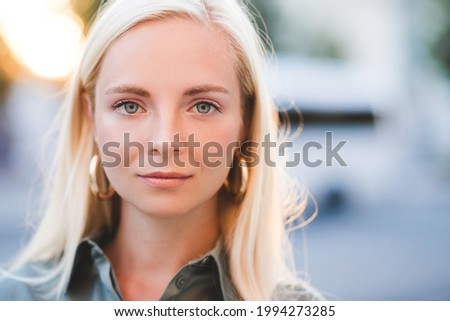 Beautiful blonde young girl 20-24 year old posing over city background close up. Looking at camera. Attractive woman with blue eyes.  Foto stock ©