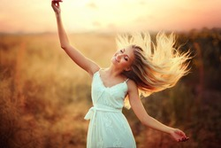Beautiful blonde young model in white dress raising hands in sun light and enjoying nature outdoors. Glow sun. Free happy woman.Flying hair.