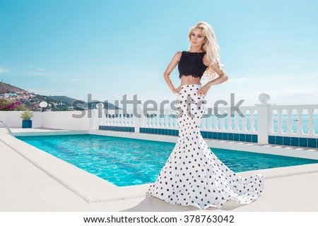 Beautiful blonde young slim woman model girl standing next to an exclusive pool and spa Willas in a long wedding dress carnival ballroom polka-dots in the island of Santorini island spain