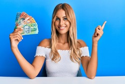 Beautiful blonde young woman holding australian dollars smiling happy pointing with hand and finger to the side