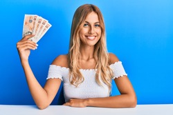 Beautiful blonde young woman holding 10 united kingdom pounds banknotes looking positive and happy standing and smiling with a confident smile showing teeth
