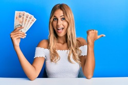 Beautiful blonde young woman holding 10 united kingdom pounds banknotes pointing thumb up to the side smiling happy with open mouth