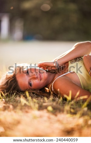 Beautiful Blonde Young Woman laying down in shade glowing skin variation hand on neck