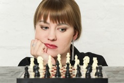Beautiful blonde young woman looks at the chess board with distant figures. Face propped with hand, close-up. The concept of female logic, mind, women in chess.