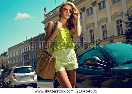 Beautiful blonde young woman wearing sunglasses, shorts, green top and handbag walking on the street