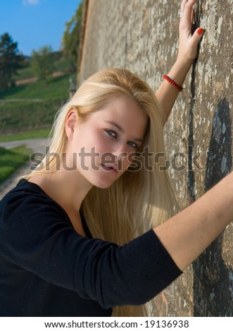 Beautiful blondy woman against on  old red brick wall