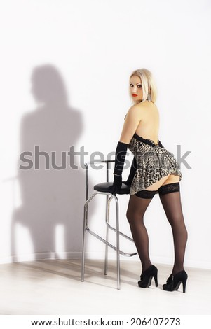 Beautiful blondy young woman in black gloves sitting on a chair close up on the white background