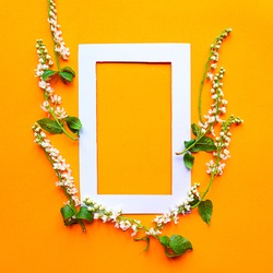 Beautiful blooming spring flowers and mockup photo frame on bright orange background. Springtime concept