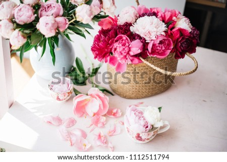 Beautiful blossoming fresh peonies in a wicker basket , tender pink peony bouquet in a vase and coral peony petals on the pink table, summer floral setup