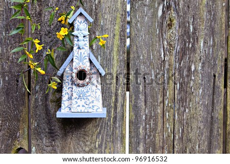 Beautiful blue and white church birdhouse on rustic wooden fence with yellow yellows