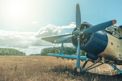 Beautiful blue and yellow airplane on a forest and sky background. Vintage aircraft.