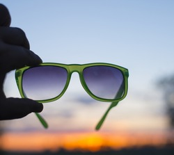 Beautiful blue and yellow sunset cloudy sky through stylish accessory  Silhouette Man's hand holding sunglasses Empty copy space for inscription