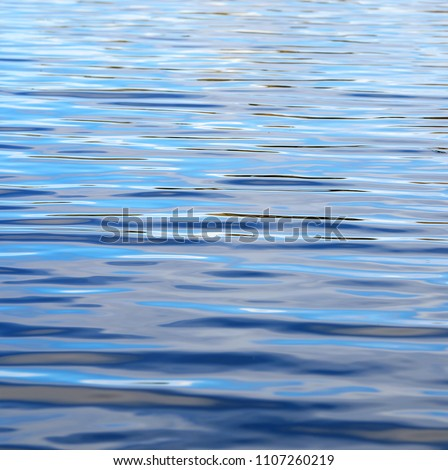 beautiful blue colored simple background of rippling water surface, calm ocean waves or flat water. Cool soothing water. H20 natures thirst quencher. inky liquid. wet sea wallpaper pattern texture