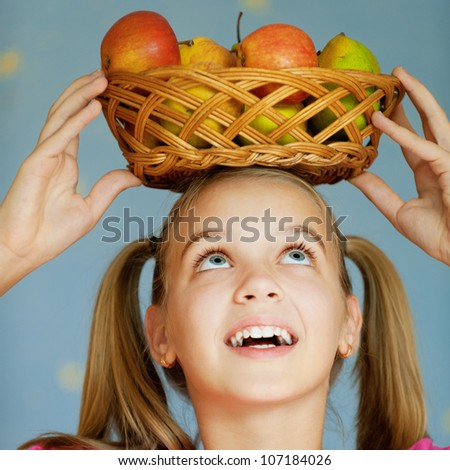 Beautiful blue-eyed laughing girl-teenager in pink dress keeps on his head basket of apples, on blue background.