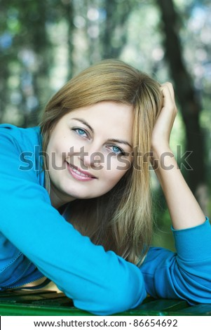 Beautiful blue-eyed smiling woman against blurred forest background with selective focus