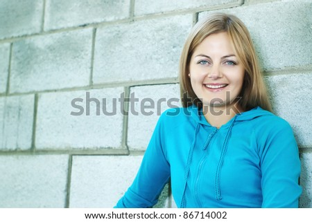 Beautiful blue-eyed smiling woman against stone wall with selective focus and copy space